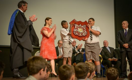 Students present a trophy to members of the Senior Leadership team at their Annual Prize Giving assembly