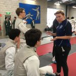 Coaches chat with members of the fencing team during the competition
