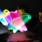 Stanmore and Wyvern students work together for a science experiment - waving bright coloured lights in a dark room
