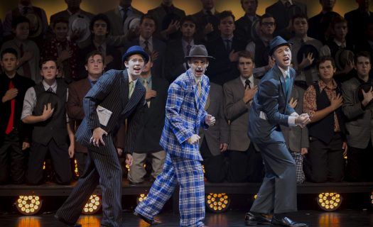 A group photo of students in costume during the production of Guys and Dolls.