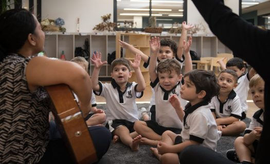 ELC students sing a song with their teacher who is playing guitar.