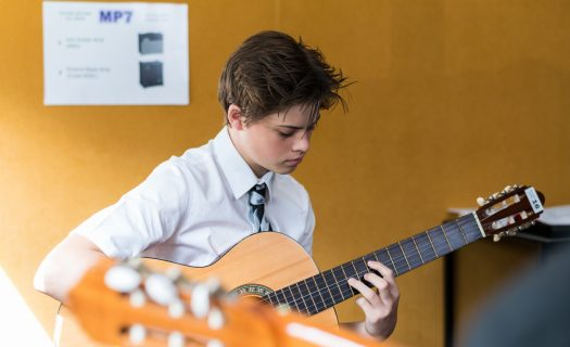 Student plays guitar in a music room on Stanmore campus.