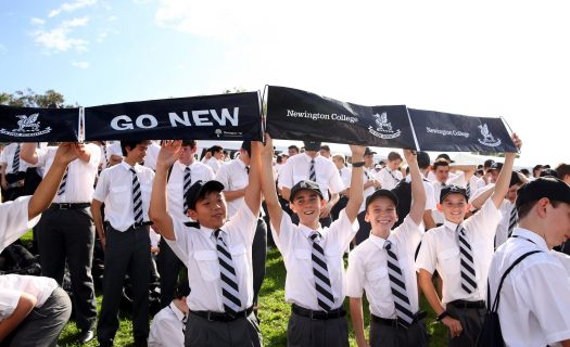 Students cheer holding ' Go New' signs at Head of the River event