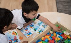 Two Early Learning Centre students play with coloured blocks for a learning activity.