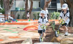 Students play on scooters in the Early Learning Centre outdoor play area.