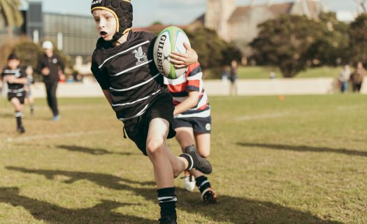 a Prep student runs with the ball on the rugby oval