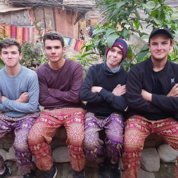 Nepal tour students pose for a small group photo wearing colourful pants.