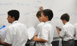 Year 7 students write their maths problems on the whiteboard of their classroom.