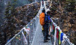 Students standing on a bridge in the Mountains of Nepal.