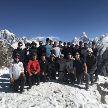 A group photo of students and teachers on top of a mountain in Nepal