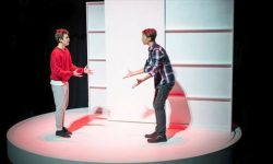Two students act on stage for the production 'Love and Information'.