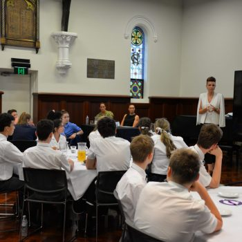 a photo of students gathered for the International Women's Day forum listening to a guest speaker