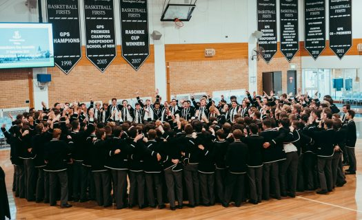 Class of 2019 in uniform gathered in a ring on the basketball courts for Valedictory, throwing their hands in the air.