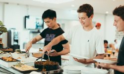 Three boys are serving themselves food from a buffet in the dining at the boarding house