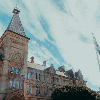 An angled image with the Australian flag in the foreground, looking up at Founders, a sandstone building with a clock tower.