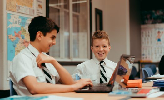 Two boys at a desk in a French classroom with a laptop open in front of them.